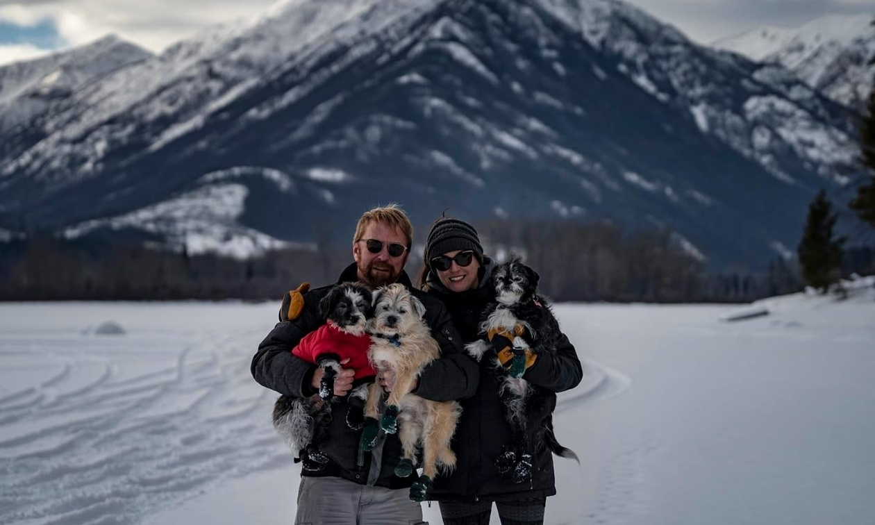 owners with their three small dogs, wearing cute little boots