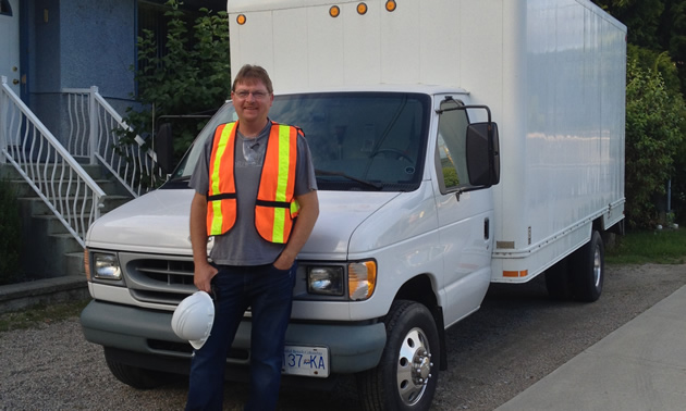 Max stands in front of a white cube van wearing a safety vest and holding a hard hat.