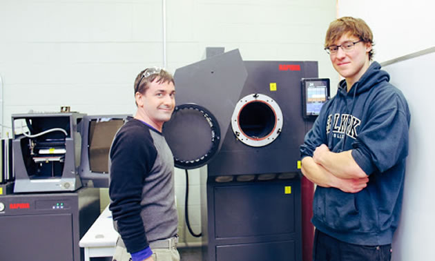 Metal printer with two people men standing beside it.
