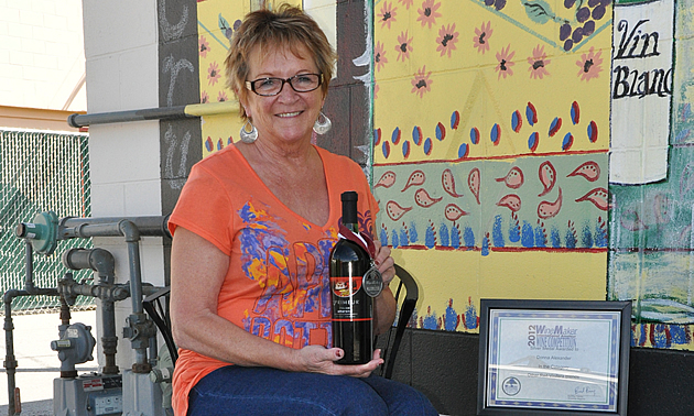 Donna Alexander sitting on a patio chair with a bottle of her award winning wine in Golden, BC
