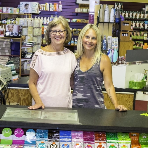 two ladies standing at a counter with nutritional supplements