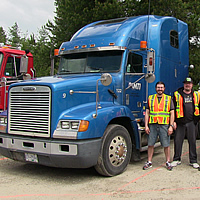 A group of trucking students standing between two big semi-trucks.