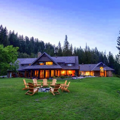 Picture of log-cabin style lodge house, with Adirondack chairs sitting on the lawn, and a treed mountainside in the background.