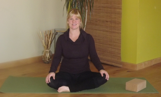 a blond woman seated on the floor in a yoga position