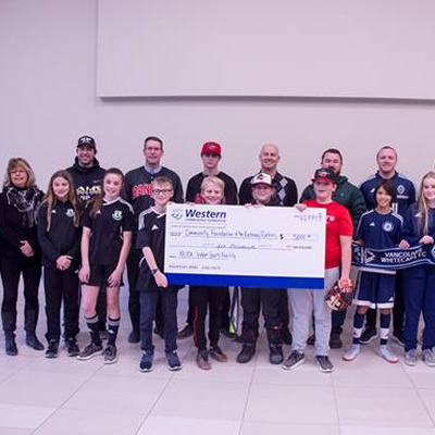 Group shot of donors, holding large cheque.