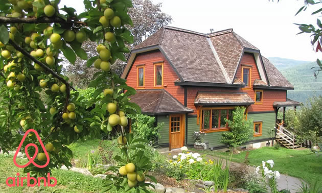 Picture of eco-house in middle of orchard, with view of lake in background.