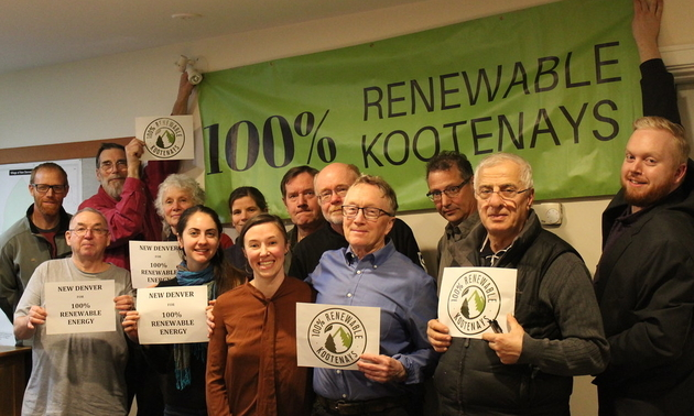 A group of New Denver citizens hold up signs in support of the 100% Renewable Kootenays campaign.