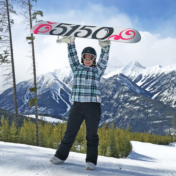 Young lady holding up a snowboard at Panorama