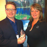 Wendy Van Puymbroeck of Kootenay Rockies presents the best marketing campaign of the year to Ian Thorley of Bellstar Hotels and Resorts.