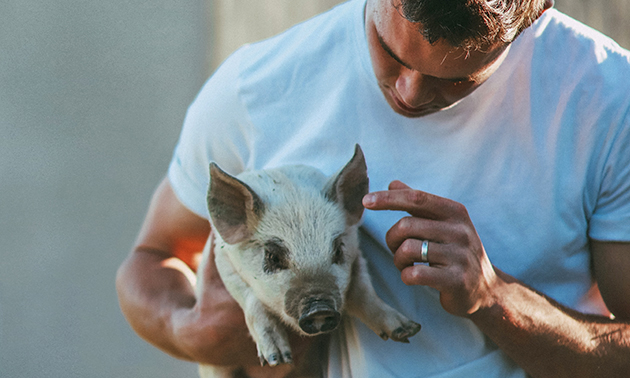 Kieran Poznikoff holding a piglet.