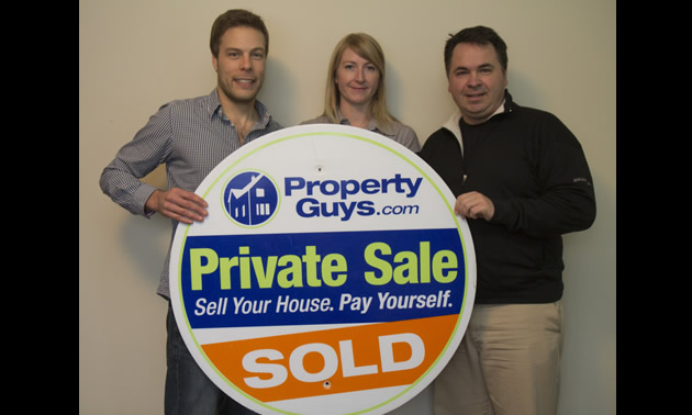 two men and a woman hold up a large round sign for PropertyGuys.com that says Private Sale: Sold