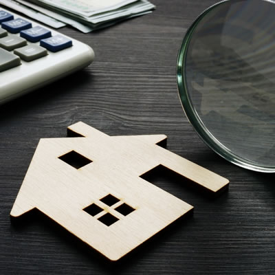 Close up of flat wooden house shape, magnifying glass and computer keyboard.