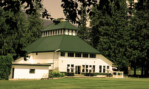 The Revelstoke Golf course clubhouse, a white building with sloping dark green roof.