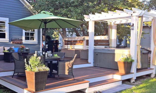 A deck by Rigby Built Construction, complete with a pergola, hot tub, and dining and living areas.