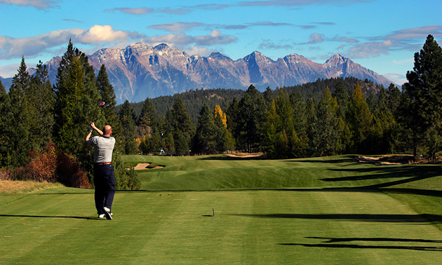Golfer taking a swing along a long fairway, with large mountains in background.