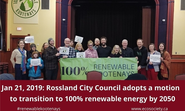 A group of Rossland citizens hold up signs in support of the 100% Renewable Kootenays campaign.