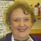 a middle-aged woman smiling behind a counter with an apron on and whiteboard with daily specials behind