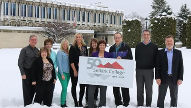 Members of the Selkirk College 50th Anniversary Committee stand in front of the Castlegar Campus with a new logo that recognizes five decades of post-secondary in the West Kootenay-Boundary.