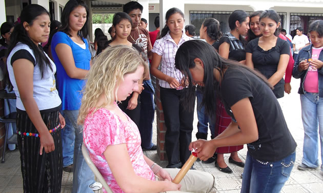 Photo of a student nurse demonstrating how to use condoms for the Sipikapense Indigenous group