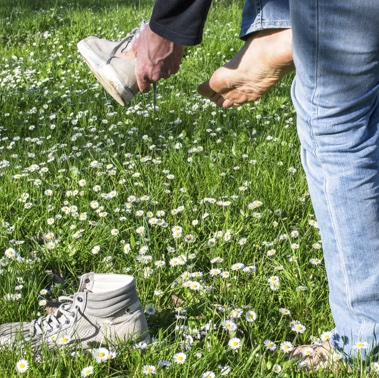 A man is taking off his runners to stand in a lawn of grass and white flowers.