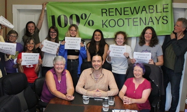 A group of Silverton citizens hold up signs in support of the 100% Renewable Kootenays campaign.