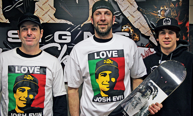 A man holding a skateboard with his brother's picture on it.