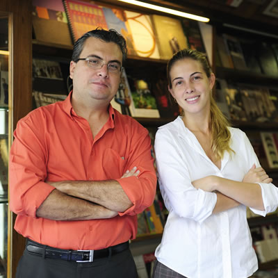 A man and a woman stand in front of shelves of books.