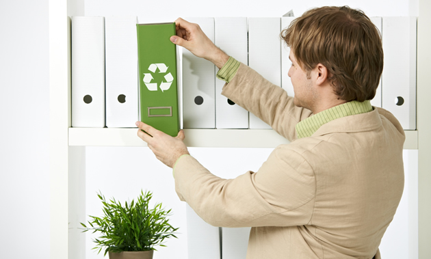 A man in a suit jacket pulls a green binder with a recycle symbol off of a shelf of white binders.