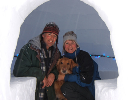 Charlie Sims, Sunny the dog and  Martina Danzer sitting in an igloo