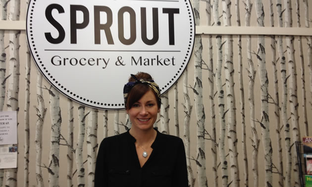 Chantel Delaney is standing in front of the Sprout Grocery sign with birch tree wallpaper on the wall.
