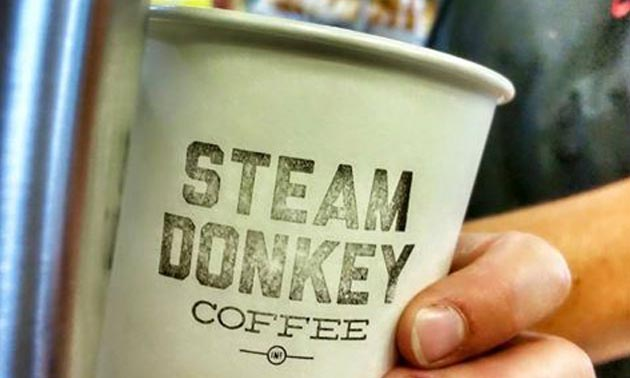 Picture of a person holding a coffee cup with the words 'Steam Donkey Coffee' printed on it.