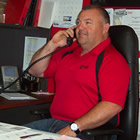 Photo of a business man in a red shirt talking on the phone at his desk.