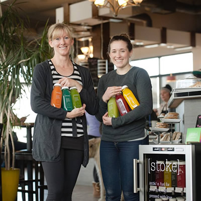 Sherry Jackson and Jill Bentley-Lobban celebrate the installation of a new [stoke] juice outlet at Cranbrook's Hot Shots Cafe.