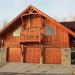 exterior of a timber frame garage with 3 garage doors