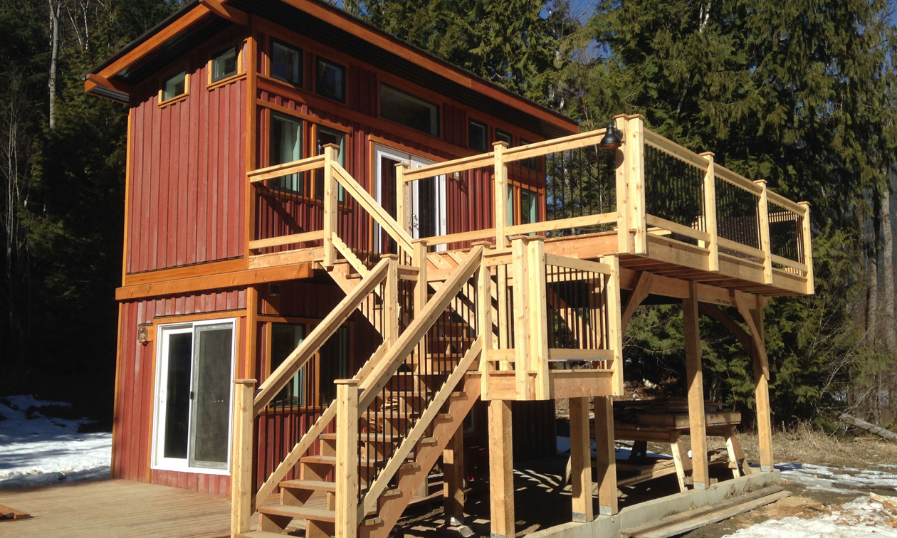A tiny two-storey house has outside stairs leading to an open deck on the second level.