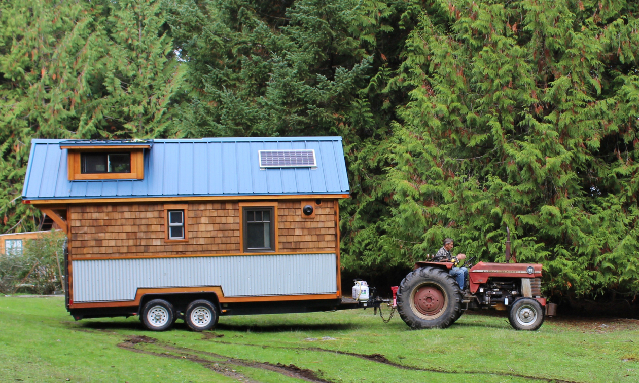 A tiny house is being pulled by a tractor.