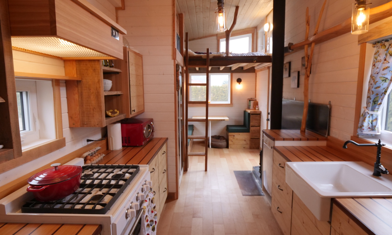 Shown is the interior of a tiny house, showing the kitchen in the foreground with lots of wood everywhere.