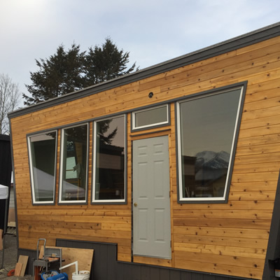 A picture of a tiny home with cedar siding.