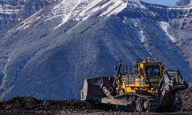 Picture of construction equipment, with snowy mountain in background.