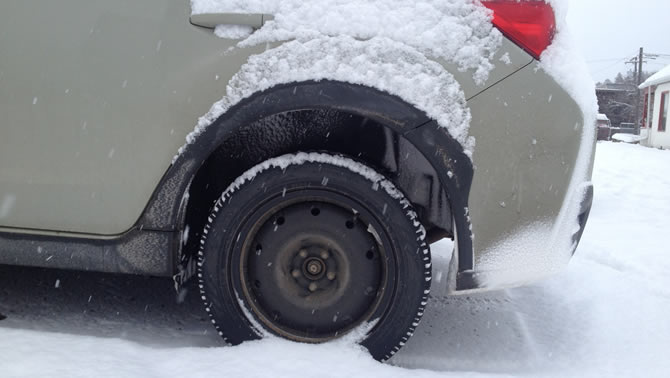 An Observe tire on a Subaru in the snow