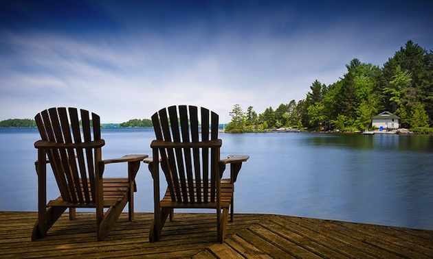 Chairs on a deck overlooking a tranquil lake.