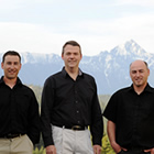 Three men in black shirts standing together with the mountains in the background.
