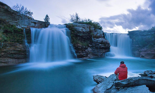 Kyle Hamilton sitting beside picturesque waterfall.