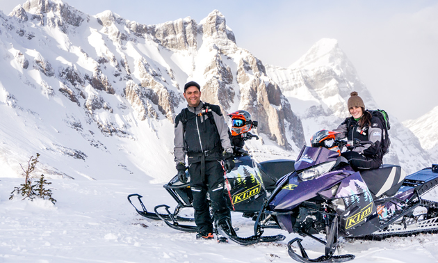 A young man and woman on snowmobiles in the mountains.