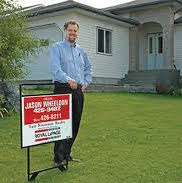 Jason Wheeldon standing next to a sold sign in front of a house.