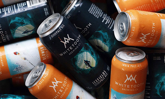 Close-up of Whitetooth Brewing Company cans.