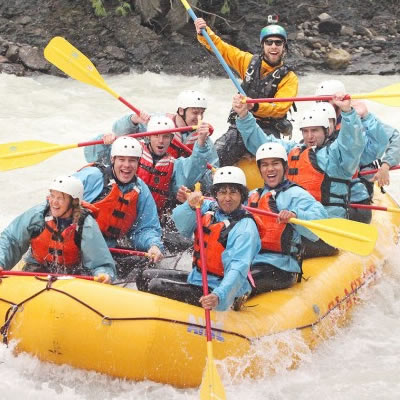 A group of whitewater rafters in a yellow raft.