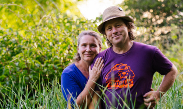 The owners of Track Street Growers standing in a field
